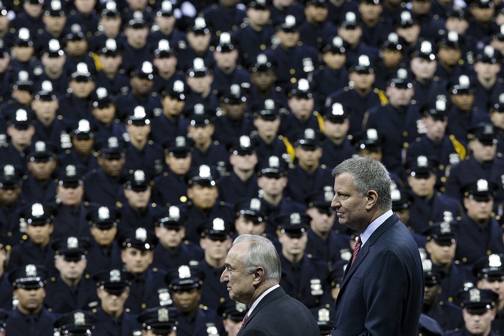 FILE - In this Dec. 29, 2014 file photo, New York City Mayor Bill de Blasio, right, and NYPD police commissioner Bill Bratton, center, stand on stage during a New York Police Academy graduation ceremony at Madison Square Garden in New York. The New York City Council is poised to renew its call to hire 1,000 more officers for the police department, potentially setting up a repeat clash with de Blasio about the headcount of the nation's largest police force. The council will release its budget presentation on Tuesday and will include funding to hire the additional officers, council staffers told The Associated Press on Sunday, April 12, 2015. (AP Photo/John Minchillo, File)