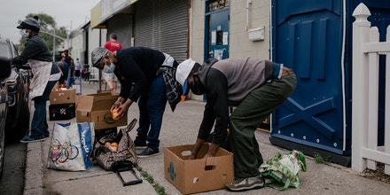 Residents in need seeking food transfer their groceries from the box supplied by the food pantry into their reusable bags outside the Children of the Light Food Bank at 1171 E 95th Street in Canarsie, New York City, New York, U.S., May 29, 2020. José A. Alvarado Jr. for The Intercept