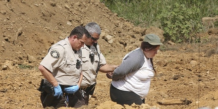 The Franklin County Sheriff's Office arrests a protestor on trespassing charges on the Mountain Valley Pipeline work site in Franklin County Thursday Thursday, August 15, 2019. Two people locked themselves to the equipment in protest of the pipeline and were charged with trespassing. (Heather Rousseau/The Roanoke Times via AP)