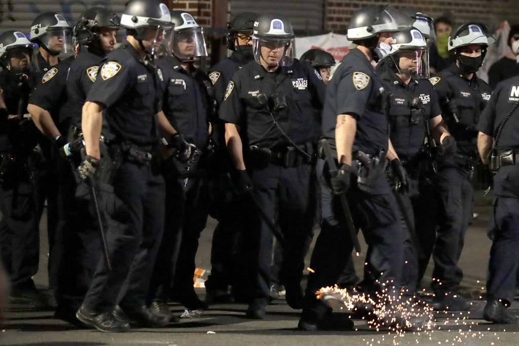 Police officers react as a firework is thrown in their midst during a protest in the Brooklyn borough of New York, Saturday, May 30, 2020. Demonstrators took to the streets of New York City to protest the death of George Floyd, a black man who was killed in police custody in Minneapolis on May 25. (AP Photo/Seth Wenig)