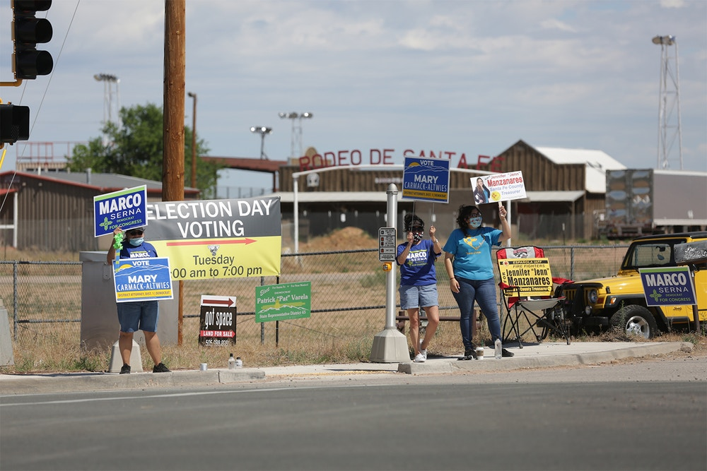 Campaigners wave signs for local and statewide Democratic candidates outside a polling place on Tuesday, June 2, 2020, in Santa Fe, New Mexico. Primaries for Democratic and Republican primary contests were held in New Mexico for the first time since the COVID-19 pandemic took hold. Poll workers wore surgical masks to prevent the spread of the virus and voters were given a squirt of hand sanitizer as they entered the building, a warehouse next to the county's rodeo grounds. (AP Photo/Cedar Attanasio)