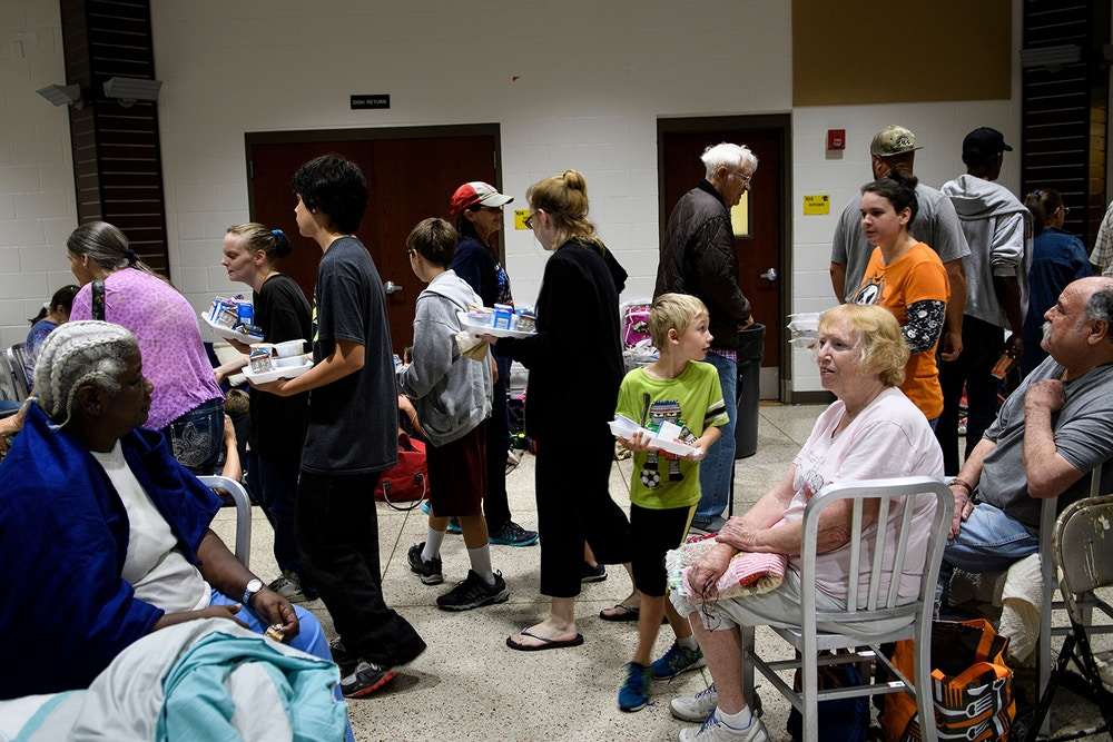 "People wait for breakfast as they and others seek safety in a shelter as Hurricane Michael approaches on October 10, 2018 in Panama City, Florida. - Hurricane Michael closed in on Florida's Gulf Coast on Wednesday as an ""extremely dangerous"" category four storm packing powerful winds and a huge sea surge, US forecasters said. The Miami-based National Hurricane Center said the storm, which local forecasters are calling an ""unprecedented"" weather event for the area, is expected to slam ashore later in the day with ""life-threatening"" storm surges. (Photo by Brendan Smialowski / AFP)        (Photo credit should read BRENDAN SMIALOWSKI/AFP via Getty Images)"