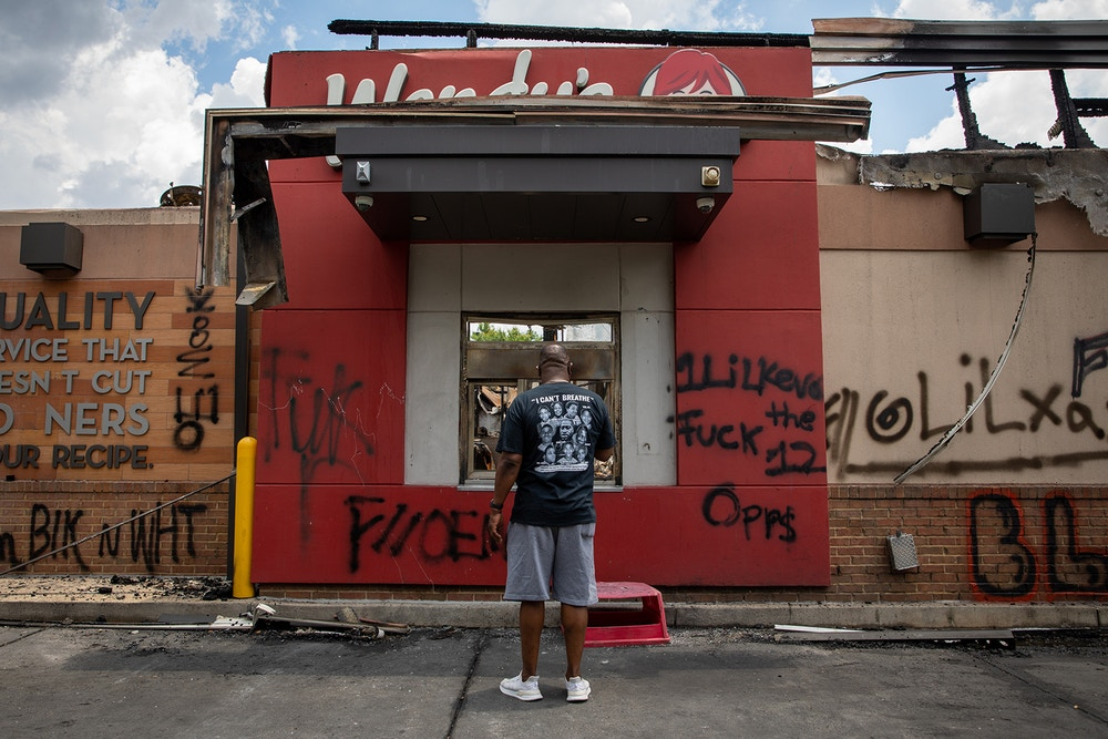 ATLANTA, GA - JUNE 14:  (EDITORS NOTE: Image contains profanity) A man stands in front of the Wendy's restaurant set ablaze overnight on June 14, 2020 in Atlanta, Georgia. Rayshard Brooks, 27, was shot and killed on June 12th by police in a struggle following a field sobriety test at the Wendy's.  (Photo by Dustin Chambers/Getty Images)