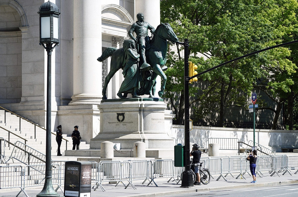 People pass by the Theodore Roosevelt Equestrian Statue, which sits on New York City public park land in front of the The American Museum of Natural History  on Central Park West entrance June 22,2020. - The American Museum of Natural History will remove the Theodore Roosevelt from its entrance after objections that it symbolizes colonial expansion and racial discrimination, Mayor Bill de Blasio said. (Photo by TIMOTHY A. CLARY / AFP) (Photo by TIMOTHY A. CLARY/AFP via Getty Images)