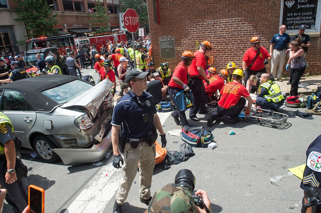 TOPSHOT - A woman is received first-aid after a car accident ran into a crowd of protesters in Charlottesville, VA on August 12, 2017. - A picturesque Virginia city braced Saturday for a flood of white nationalist demonstrators as well as counter-protesters, declaring a local emergency as law enforcement attempted to quell early violent clashes. (Photo by Paul J. RICHARDS / AFP)        (Photo credit should read PAUL J. RICHARDS/AFP via Getty Images)