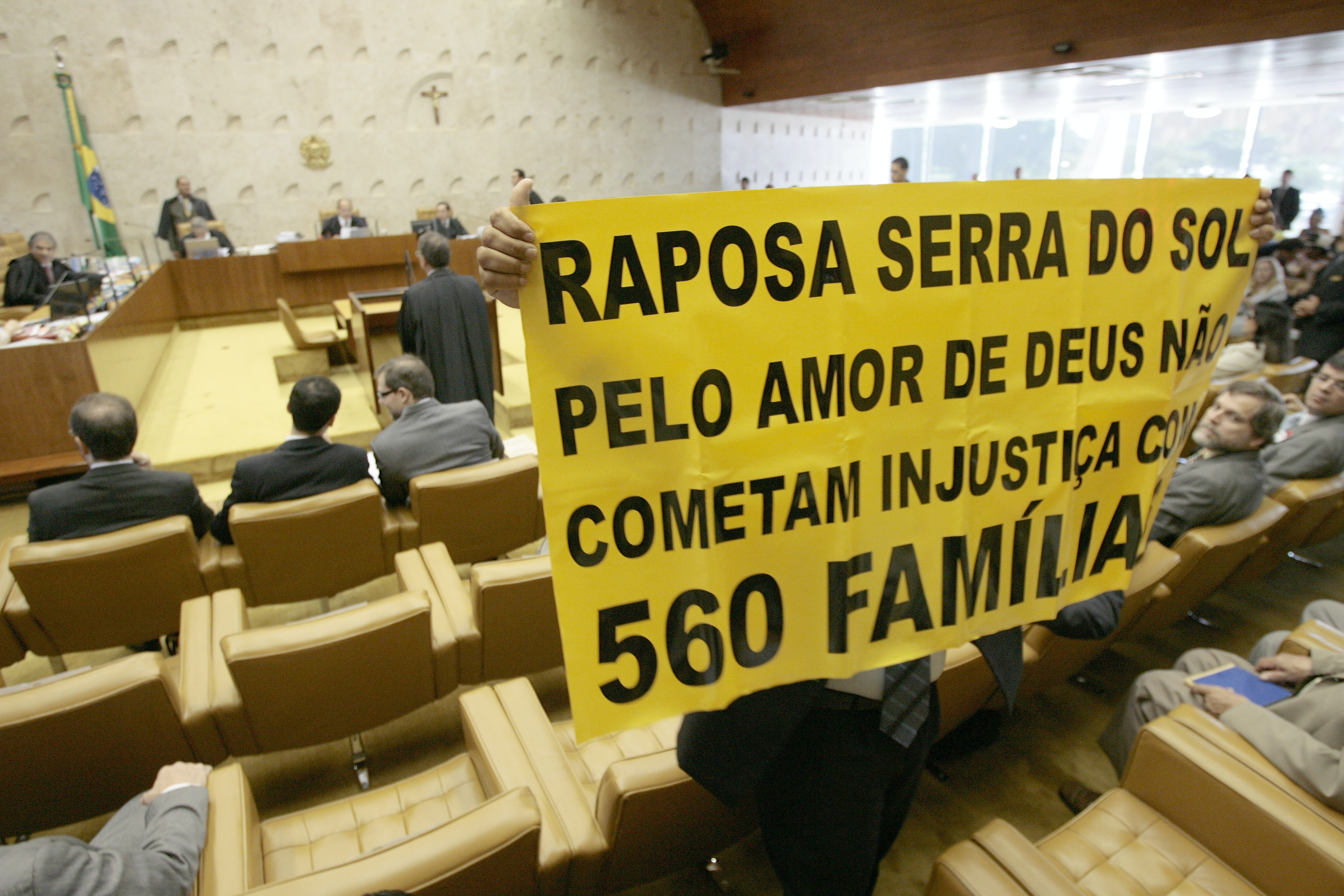 "A representative of a group of farmers who oppose a resolution of Brazil's Supreme Court, confirming that the Raposa Serra do Sol reservation in northern Brazil must remain intact, holds a sign during a court's session in Brasilia, Thursday, March 19, 2009. The court ruled Thursday that the reservation must remain intact, a ruling seen as bolstering indigenous rights, and which sets an important precedent for laying out and protecting the boundaries for many Indian reserves in Brazil.The sign reads in Portuguese: ""Raposa Serra do Sol, for the love of God don't commit injustice for 560 families"".(AP Photo/Eraldo Peres)"