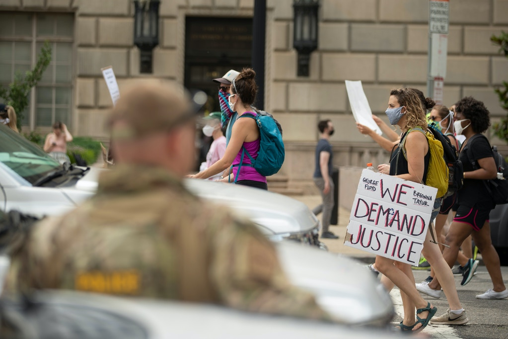 U.S. Customs and Border Protection police watch as demonstrators protest, Saturday, June 6, 2020, in Washington, over the death of George Floyd, a black man who was in police custody in Minneapolis. Floyd died after being restrained by Minneapolis police officers. (AP Photo/Andrew Harnik)