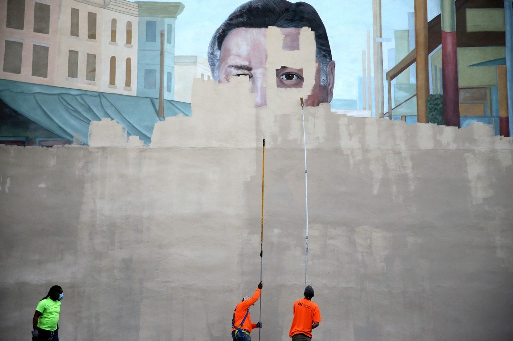 A crew from Mural Arts paints over the Frank Rizzo mural on 9th Street in Philadelphia