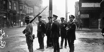 View of five policemen and one soldier with a rifle, standing on a street corner during a race riot in the Douglas community area of Chicago, Illinois, circa 1919.