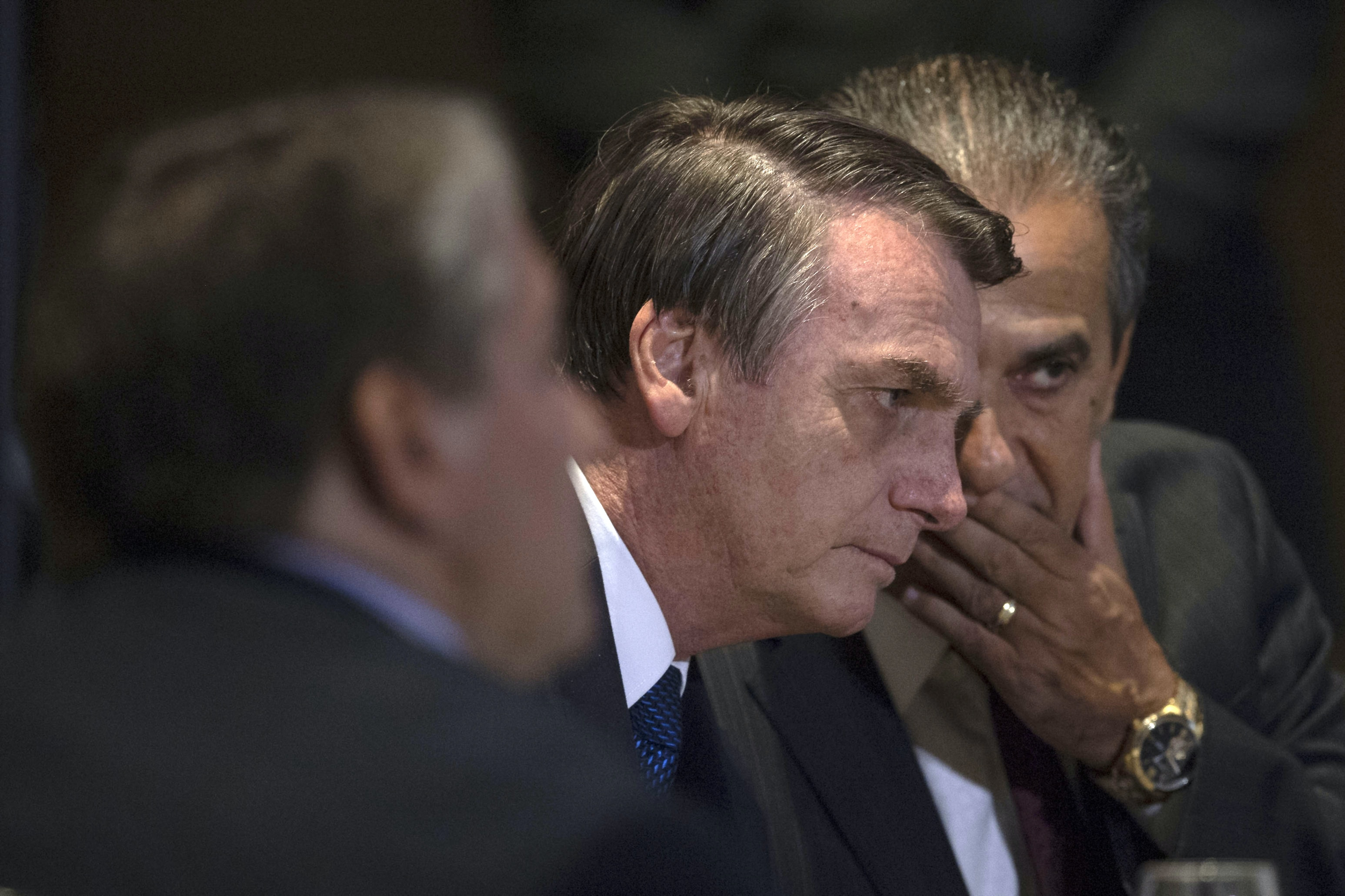 Brazilian President Jair Bolsonaro speaks with Brazilian Congressman and Bishop Silas Malafaia (R) during a meeting with evangelical leaders at the Hilton Barra Hotel, in Barra da Tijuca neighborhood, Rio de Janeiro, Brazil on April 11, 2019. (Photo by Mauro Pimentel / AFP)        (Photo credit should read MAURO PIMENTEL/AFP via Getty Images)