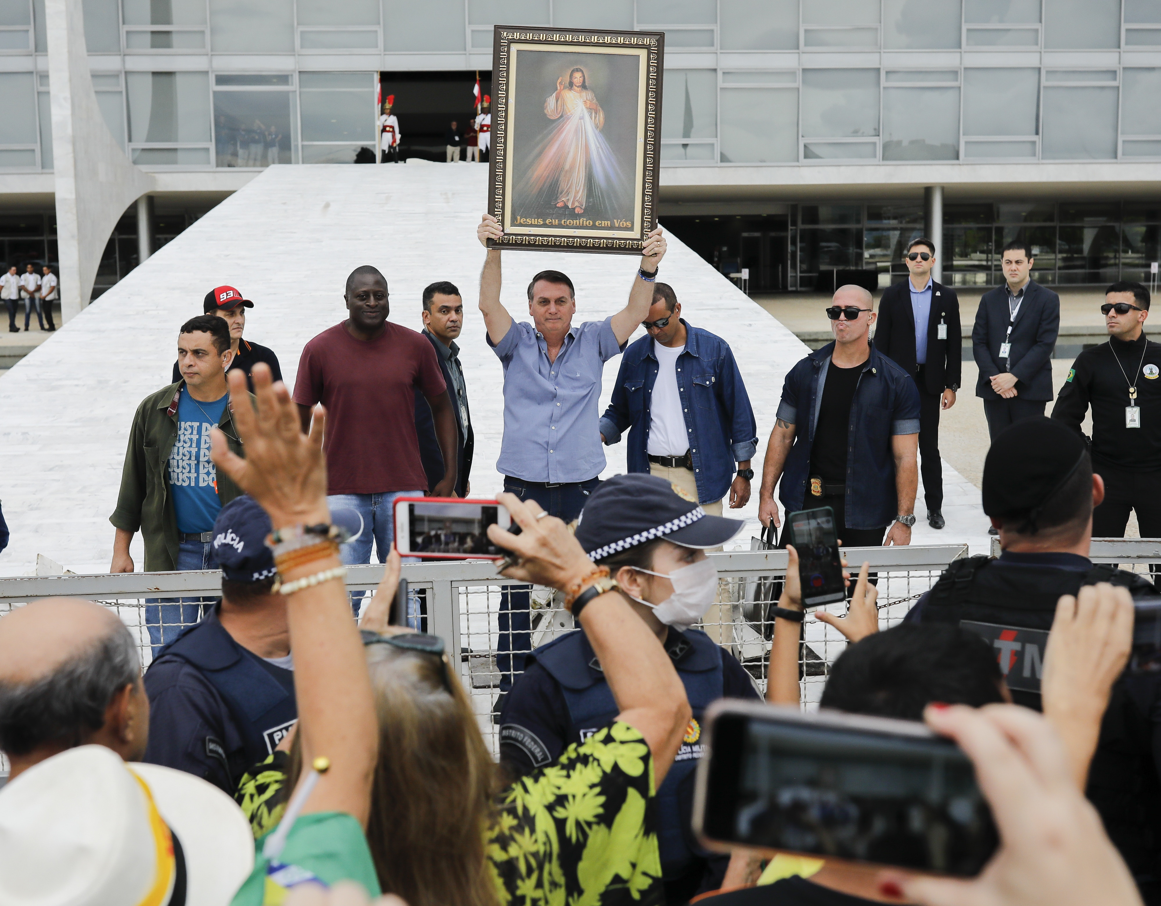 Brazilian President Jair Bolsonaro raises an image of Jesus Christ during a gathering with Catholic and anti-abortion supporters in front of Planalto Palace in Brasilia on April 18, 2020 amid the coronavirus COVID-19 pandemic. - Brazilian President Jair Bolsonaro on Friday defended his decision to restart economic activity in the middle of the coronavirus pandemic, after sacking his health minister over differences in how to tackle the disease. (Photo by Sergio LIMA / AFP) (Photo by SERGIO LIMA/AFP via Getty Images)