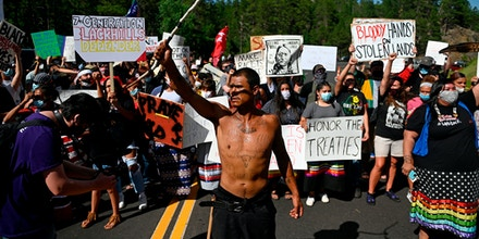 Activists and members of different tribes from the region block the road to Mount Rushmore National Monument as they protest in Keystone, South Dakota on July 3, 2020.