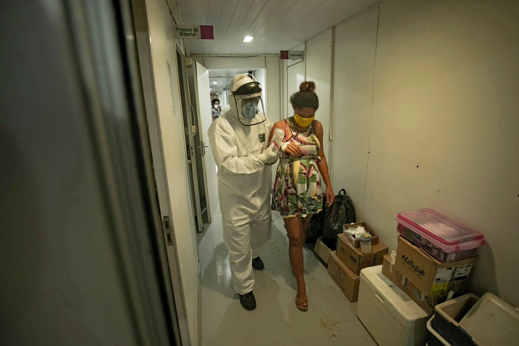 A worker from the Special Secretariat for Indigenous Health assists 19-year-old Janete Vasconcelos da Silva, an indigenous woman from the Tupinamba tribe and 8 months pregnant and who has been diagnosed with the novel coronavirus, after bringing her to a hospital in Santarem, Para State, Brazil on July 17, 2020.