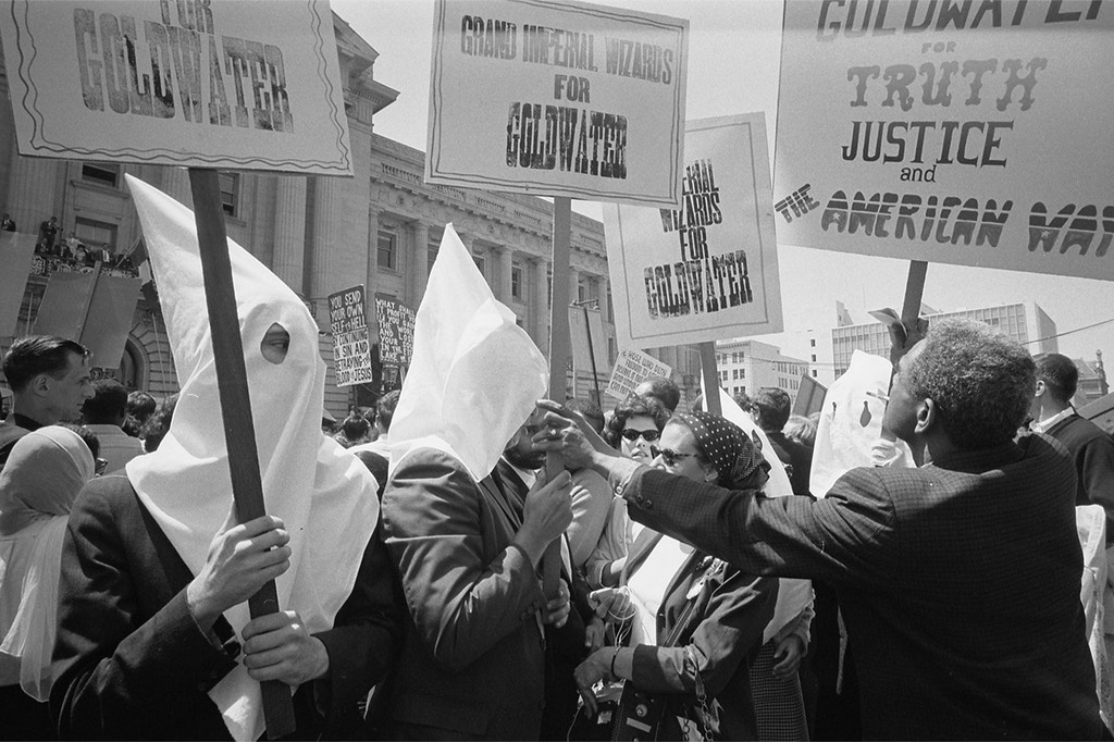 UNSPECIFIED - CIRCA 1754: Ku Klux Klan members supporting Barry Goldwater's campaign for the presidential nomination at the Republican National Convention, San Francisco, California, as an African American man pushes signs back: 12 July 1964. Photographer: Warren K Leffler. (Photo by Universal History Archive/Getty Images)