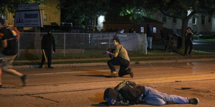 KENOSHA, WISCONSIN, USA - AUGUST 25: A man on the ground was shot in the chest as clashes between protesters and armed civilians who protect the streets of Kenosha against the arson during the third day of protests over the shooting of a black man Jacob Blake by police officer in Wisconsin, United States on August 25, 2020. (Photo by Tayfun Coskun/Anadolu Agency via Getty Images)