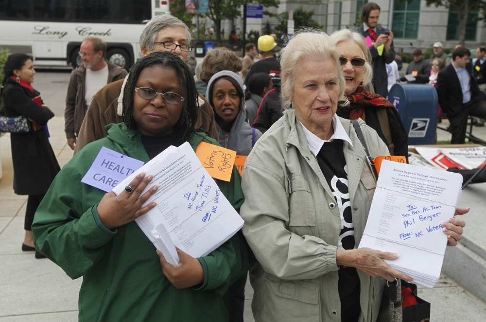 "Rev. Yvonne McJetters, left, and Sarah Huffman carry copies of a petition with 4,000 signatures to Speaker Thom Tillis and President Pro Tem Phil Berger's offices at the North Carolina General Assembly building in Raleigh, N.C.  on Monday, April 23, 2012. A coalition of political watchdog groups gathered for the second ""Rein Them In"" rally prior to the noon start of a special legislative session. The petition calls on Tillis and Berger to oppose the enactment of a government-photo ID requirement and other legislation that will make it more difficult for registered voters to cast their ballots. (AP Photo/The News & Observer, Shawn Rocco)"