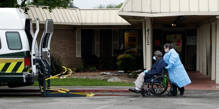 A resident is removed from the Southeast Nursing and Rehabilitation Center in San Antonio, Friday, April 3, 2020. More than 50 residents and staff have tested positive for COVID-19 at the facility. (AP Photo/Eric Gay)