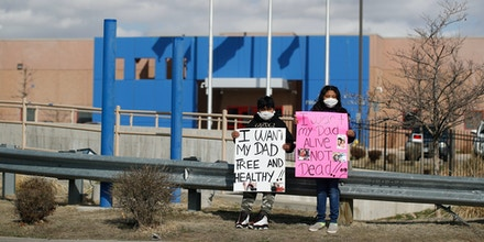 Protesters stand outside the GEO Detention Center on April 3, 2020, in Aurora, Colo.