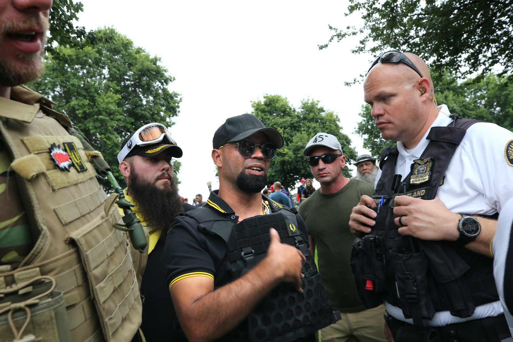 Enrique Tarrio (L), chairman of the alt-right group Proud Boys, speaks with a police officer during the End Domestic Terrorism rally at Tom McCall Waterfront Park on August 17, 2019 in Portland, Oregon.