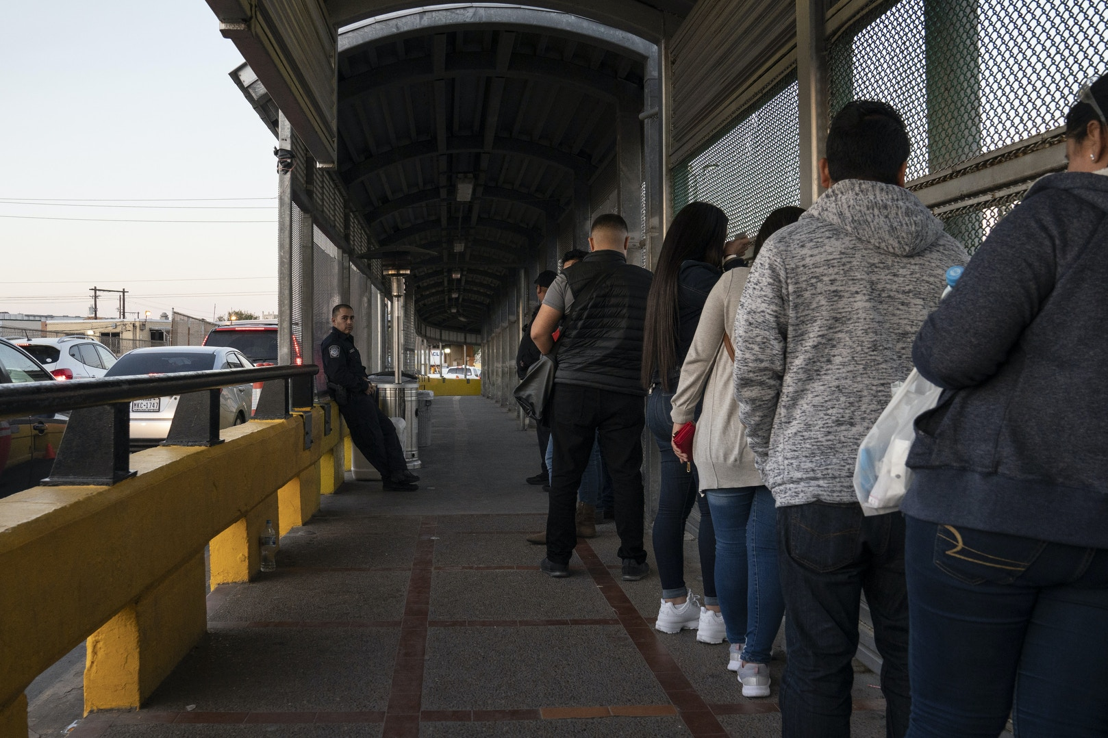 A U.S. Customs and Border Protection agent standing in the U.S. is seen from the Mexican side of the international bridge as people wait to be allowed to cross into the country in Matamoros, Mexico on Feb. 13, 2020.