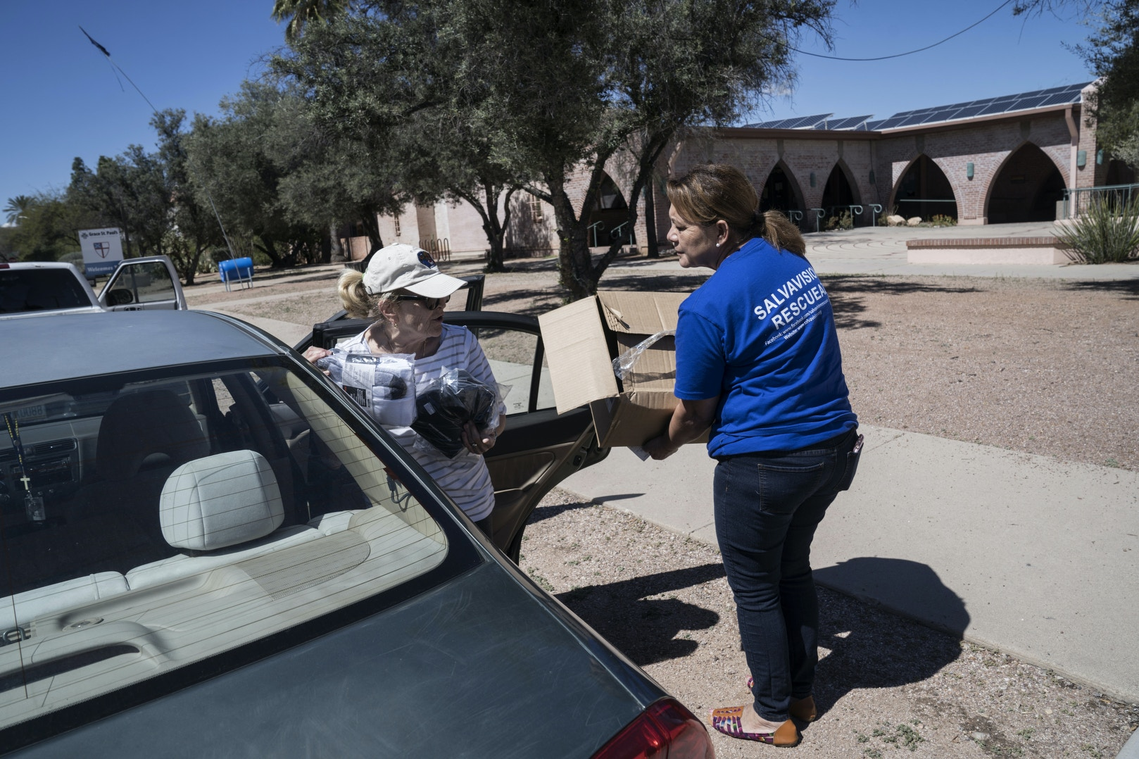 TUCSON, AZ - MARCH 14, 2020:Dora Rodriguez receives donations from Peggie Felici-Gessner, a volunteer at the Casa Alitas shelter that caters to asylum seekers in Tucson, Arizona on March 14, 2020. Ever since President Trump enacted the Remain in Mexico policy shelters on the U.S. side of the border have been trying to get their supplies and donations to camps in Nogales and other border cities where asylum seekers are living. In 1980 19-year-old Dora Rodriguez, from El Salvador, made the difficult journey of crossing into the US near Lukeville, AZ on foot. Of the 26 individuals she crossed the Sonoran desert with 13 died in the gruelling heat, one of the pre-eminent events that led to the Sanctuary Movement. Dora eventually naturalized in the US and started an advocacy group, Salvavision Rescue Arizona, to support asylum-seekers. On a weekly basis Dora visits asylum seekers in detention, writes them letters, fundraises and brings donated supplies to the migrant camps on the Mexican side of the US - Mexico border. Photo by Kitra Cahana/MAPS for The Intercept