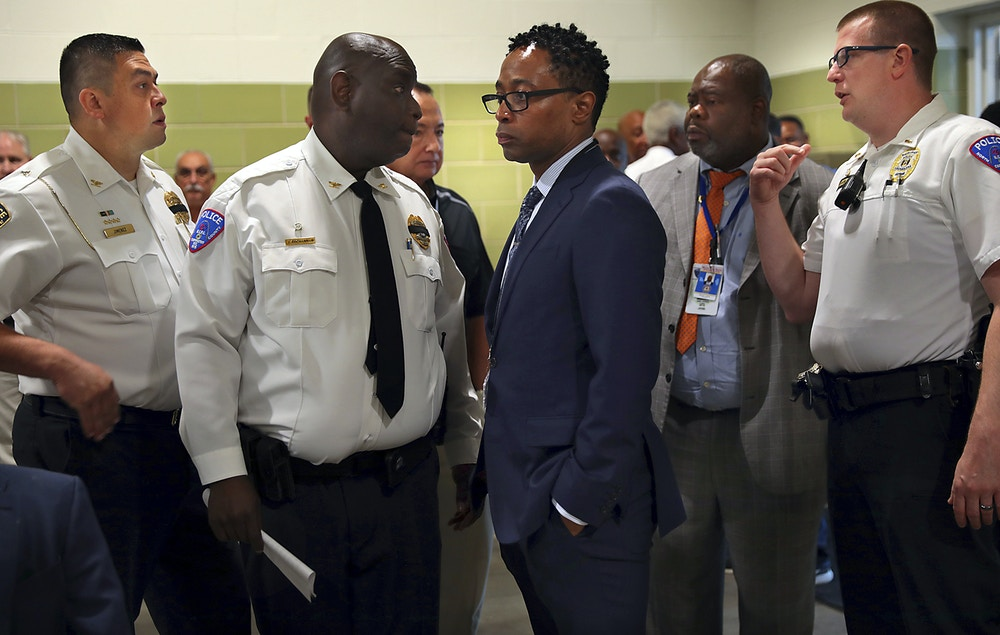 St. Louis County Prosecutor Wesley Bell, center, is surrounded by area police chiefs, including North County Police Cooperative Chief John Buchannan, second left, and St. Ann Police Chief Aaron Jimenez, left, befoer a news conference about fallen police officer Michael Langsdorf held at Beyond Housing on Monday, June 24, 2019. Langsdorf was shot and killed by a man trying to pass a bad check at Clay's Wellston Food Market on Sunday. (Robert Cohen/St. Louis Post-Dispatch via AP)