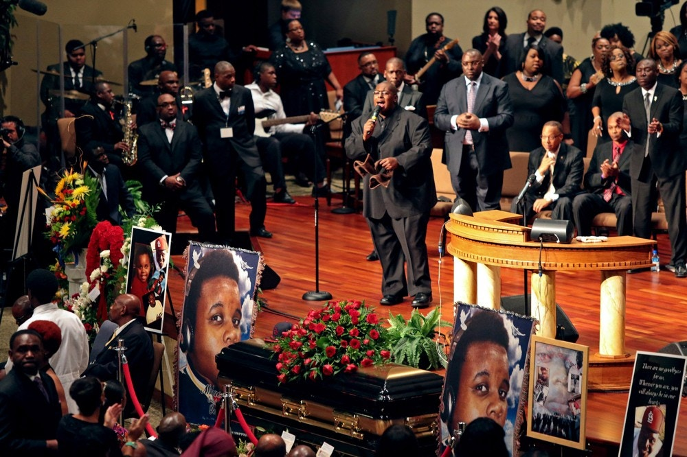 Pictures of Michael Brown flank his casket during his funeral, Monday, Aug. 25, 2014, at Friendly Temple Missionary Baptist Church in St. Louis. Hundreds of people gathered to say goodbye to Brown, who was shot and killed by a Ferguson, Mo., police officer on Aug. 9. The more than two weeks since Brown's death have been marked by nightly protests, some violent and chaotic, although tensions have eased in recent days. (AP Photo/St. Louis Post Dispatch, Robert Cohen, Pool)