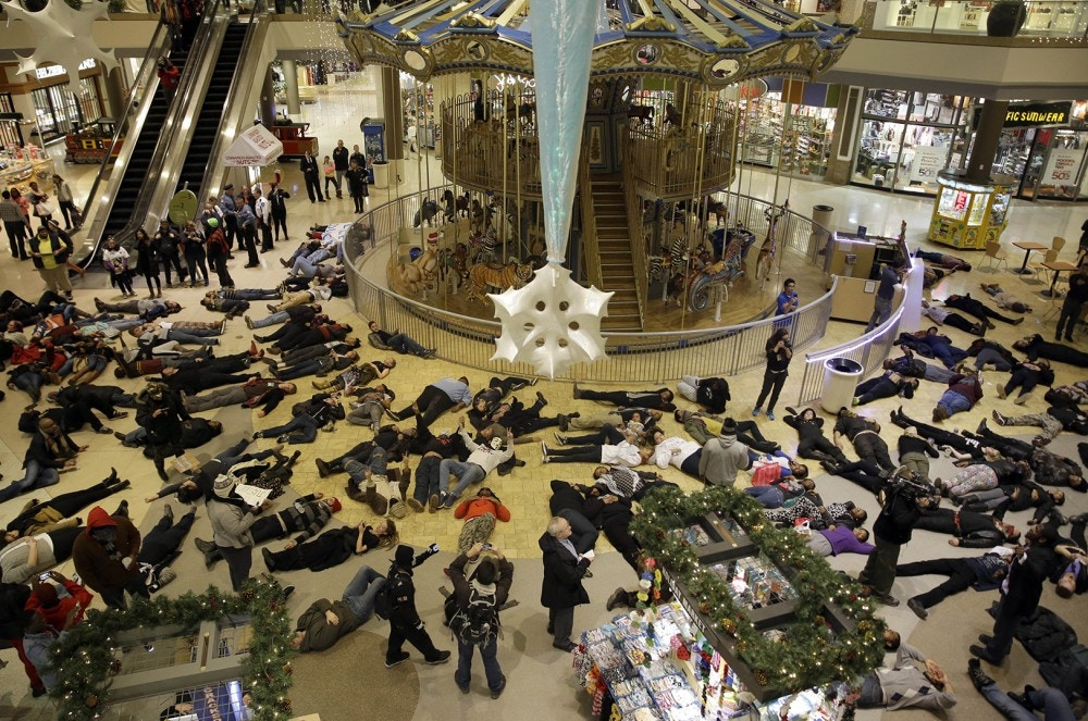 "Protesters stage a ""die in"" inside Chesterfield Mall, Friday, Nov. 28, 2014, in Chesterfield, Mo. The crowd disrupted holiday shopping at several locations on Friday amid a protest triggered by a grand jury's decision not to indict the police officer who fatally shot Michael Brown in nearby Ferguson. (AP Photo/Jeff Roberson)"