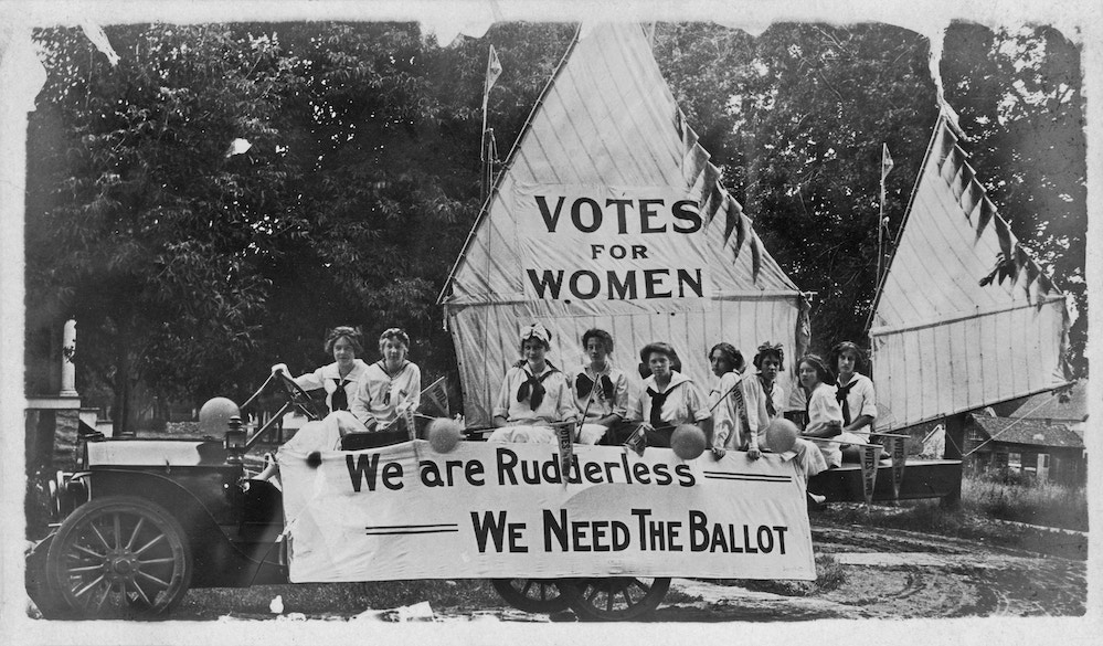 """Black and white photograph showing a group of young female suffragists, wearing sailor costumes, seated on a float decorated to resemble a boat, the mainsail reads """"Votes for Women, """" and the marquee reads """"We Are Rudderless - We Need The Ballot"""", 1900. (Photo by Ken Florey Suffrage Collection/Gado/Getty Images)"""