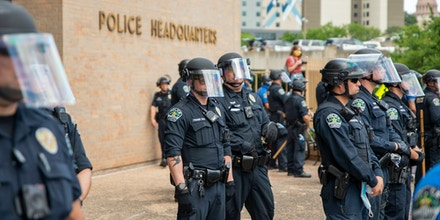 Police officers watch protesters demonstrating against police brutality outside of City of Austin Police Department headquarters in downtown in Austin, Texas on May 30, 2020.