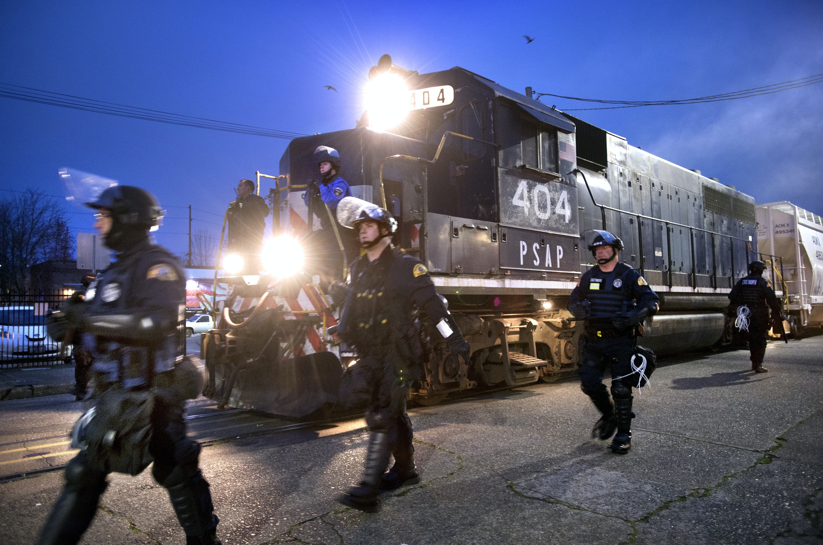 Law enforcement officers escort a train as it moves from the Port of Olympia through downtown Olympia, Wash., on Nov. 18, 2016.