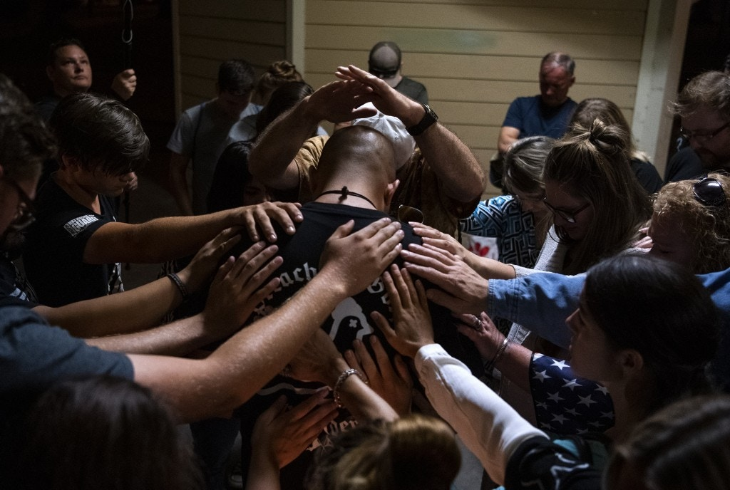 "A group gathers around Patriot Prayer leader Joey Gibson for a prayer after a candlelight vigil Saturday, Sept. 5, 2020, in Vancouver, Wash., for Aaron ""Jay"" Danielson, who was fatally shot in Portland, Ore."