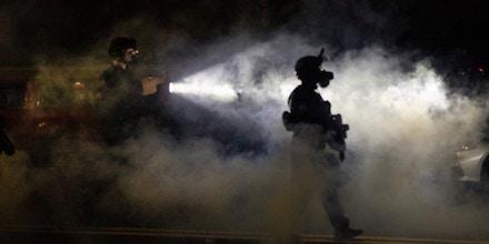 Portland police walk through a smokey street in Oregon.