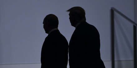 US President Donald Trump (R) walks with Russia's President Vladimir Putin before taking a family photo at the G20 Summit in Osaka on June 28, 2019.