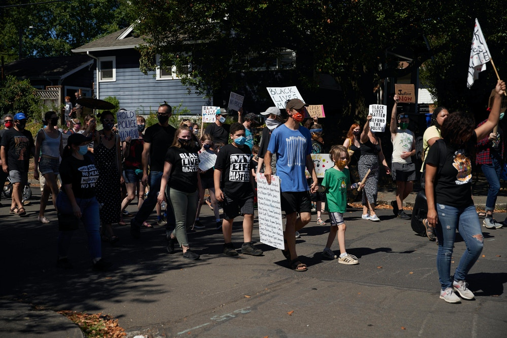 Families protest and carry signs for BLM in Portland, Oregon.