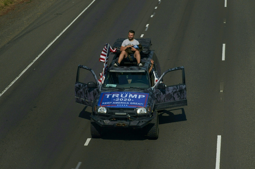 Trump supporter is seen sitting on top of car while driving down a highway in Oregon City, Oregon.
