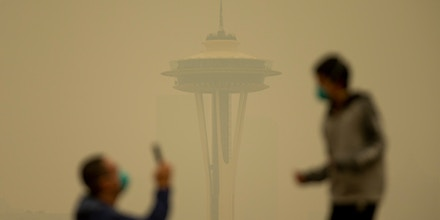 People take photos against the backdrop of the Space Needle as smoke from wildfires fills the air at Kerry Park.