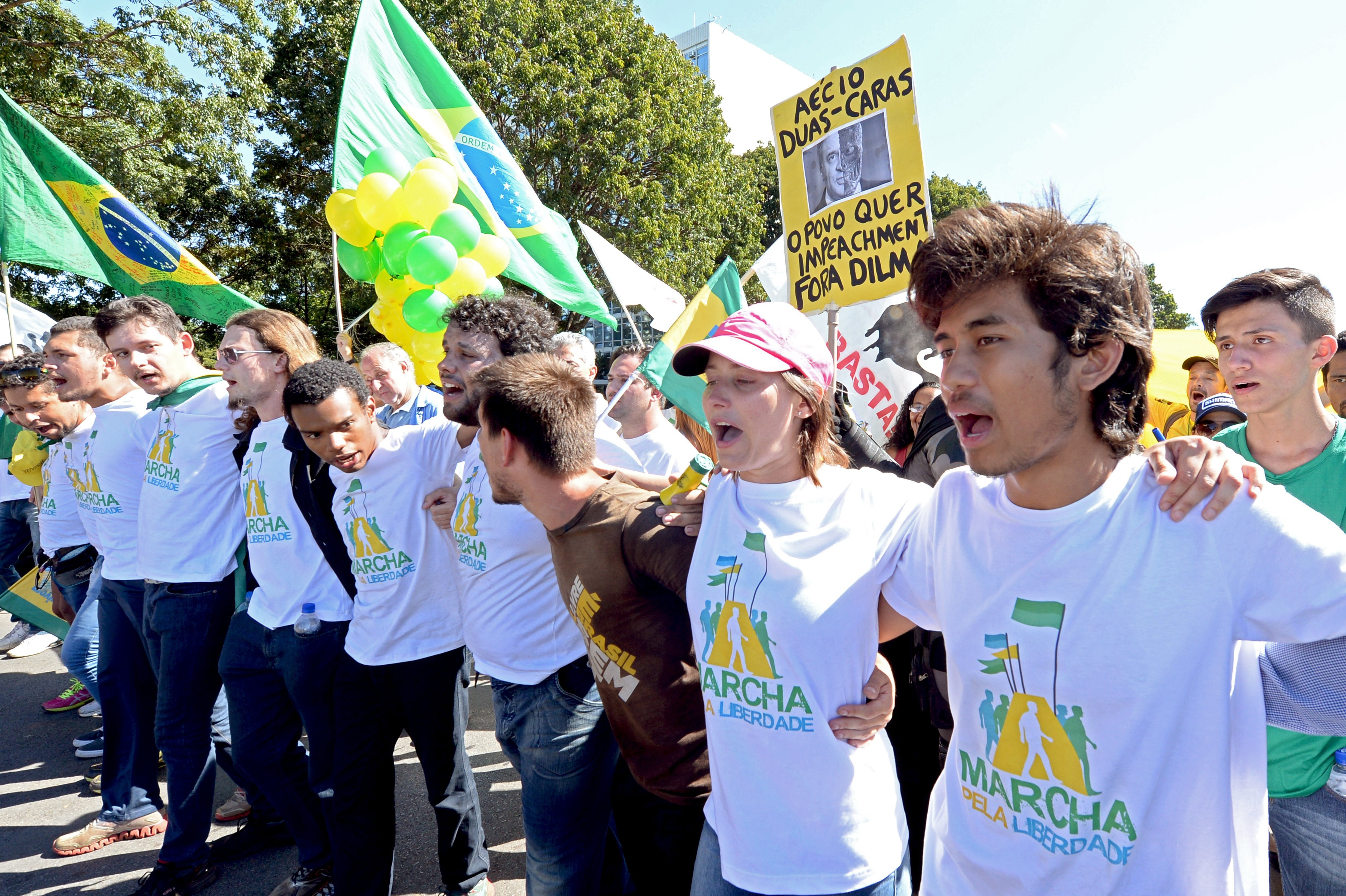 Kim Kataguiri (R), leader of the Free Brazil Movement (MBL), takes part in the March for Freedom in demand of President Dilma Rousseff's impeachment in Brasilia, Brazil on May 27, 2015. Kataguiri, a 19-year-old college drop out, is the face of MBL, a growing force which seeks to harness some of the energy of the 2013 protest movement which brought more than a million onto the streets. AFP PHOTO/EVARISTO SA        (Photo credit should read EVARISTO SA/AFP via Getty Images)