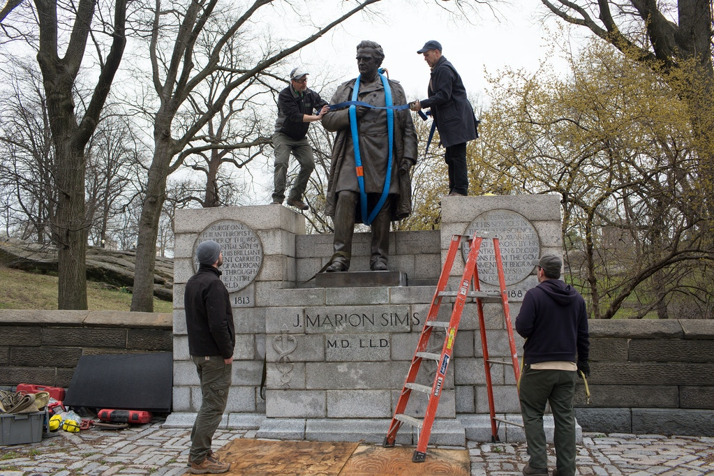 In front of a small crowd of activists and media, city workers remove a statue of J. Marion Sims, a surgeon and medical pioneer in the field of gynecology, from its perch on the edge of Central Park on April 17, 2018 in Harlem, New York.