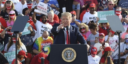 """Maurice Symonette, the founder of """"Blacks for Trump,"""" smiled from the bleachers behind President Donald Trump at a rally in Ocala, Fla., on October 16, 2020."""