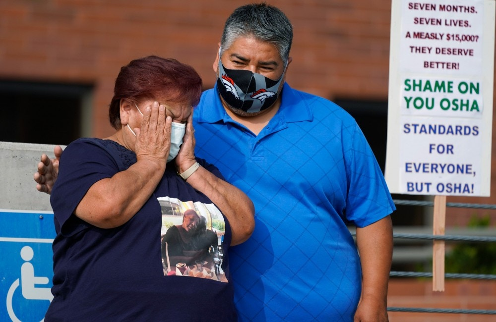 Carolina Sanchez, left, is comforted by her son, Saul, both of Greeley, Colo., during a protest staged by the union representing employees at a Colorado meatpacking plant where six workers died of COVID-19 and hundreds more were infected this past spring outside the offices of the Occupational Safety and Health Administration Wednesday, Sept. 16, 2020, in downtown Denver. Carolina Sanchez's husband, Saul, was the first worker to die of COVID at the JBS Foods plant in Greeley. (AP Photo/David Zalubowski)
