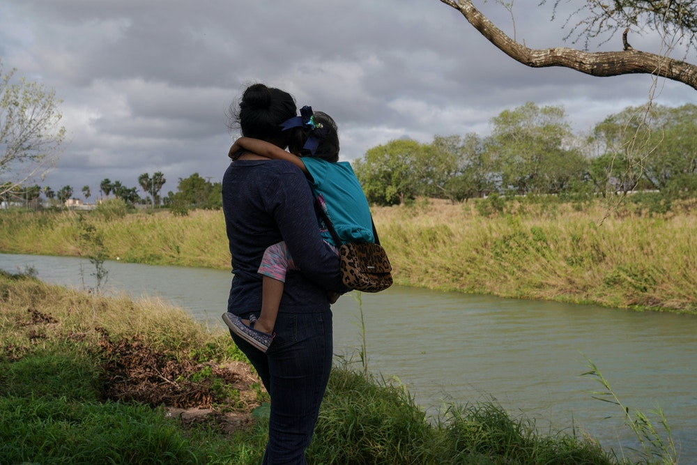 "Rocio carries her four-year-old daughter, Patricia, in an encampment where they live in Matamoros, Mexico on Feb. 23, 2020. The following day Rocio and her family were sent back to Mexico after their court hearing. They were kidnapped for two months the first time they were sent back under the ""Remain in Mexico"" program to wait for their asylum case to be decided last year.Verónica G. Cárdenas for The Intercept"