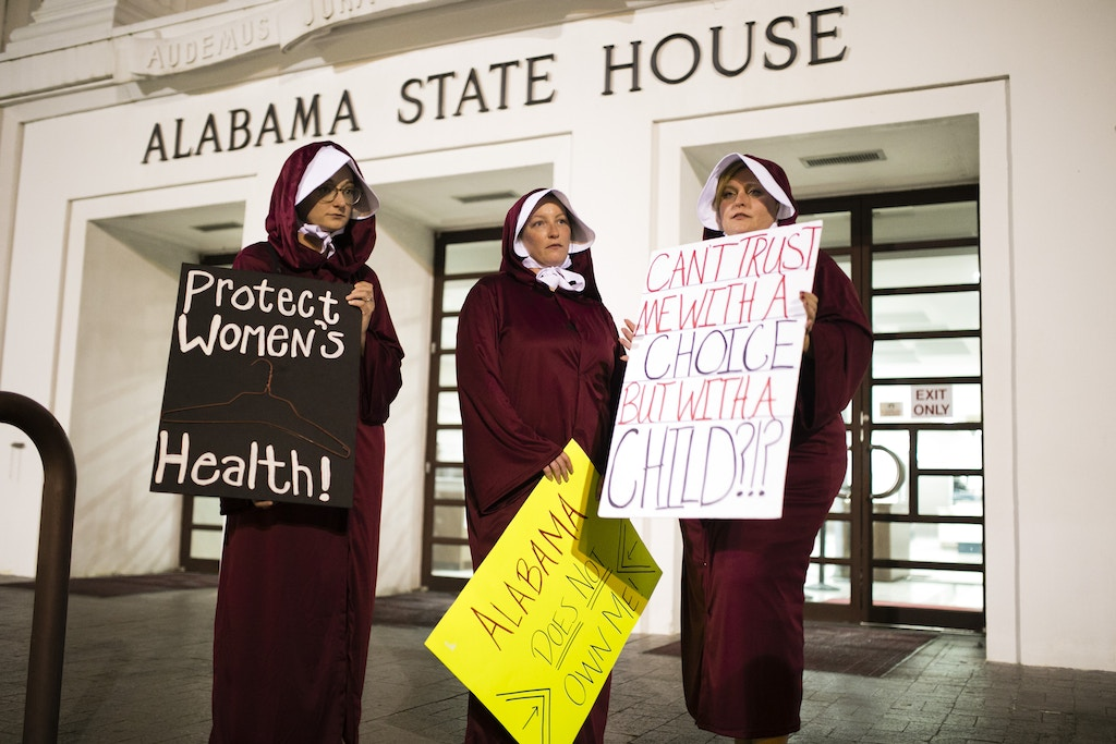 Women wearing Handmaid costumes protest in front of the Alabama State House after the State Senate passed HB314, which banned abortions in all cases except the health of the mother in the Alabama State House on May 14, 2019 in Montgomery, AL.