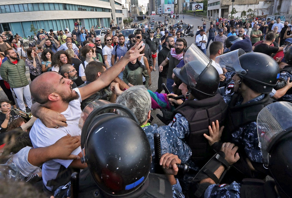 "Lebanese security forces contain clashes between demonstrators and counter-protesters in the centre of the capital Beirut during the 13th day of anti-government protests on October 29, 2019. - Dozens of rioters descended on to Riad al-Solh Square near the government headquarters in Beirut, where they attacked protesters, torched tents, and tore down banners calling for ""revolution"", said an AFP correspondent in the area. The unprecedented attack on the main site of the capital's largely peaceful protest movement forced the army and riot police to deploy en masse to contain the violence (Photo by - / AFP) (Photo by -/AFP via Getty Images)"