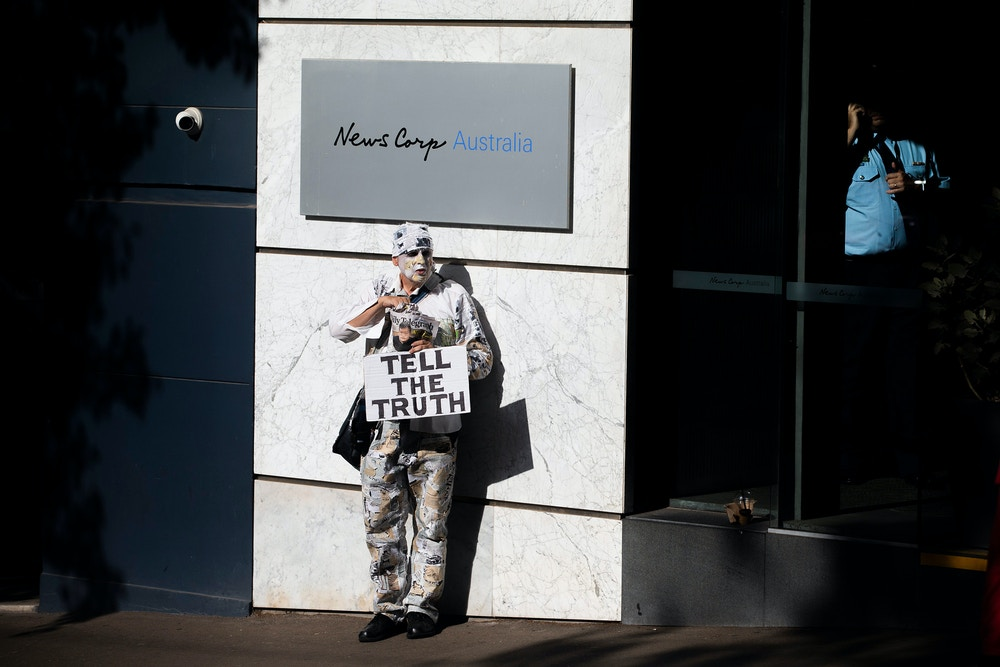 "SYDNEY, AUSTRALIA - JANUARY 31: A protester is seen at the offices of News Corp Australia in Surry hills on January 31, 2020 in Sydney, Australia. The""lie-in"" was organised to protest against what activists say are lies published across Rupert Murdoch's News Corp media outlets.  (Photo by Jenny Evans/Getty Images)"