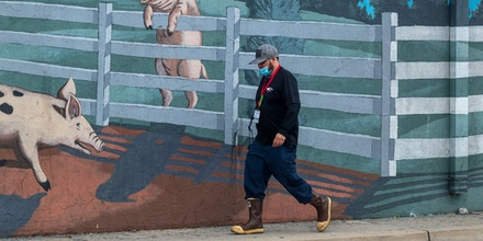 A walks past a mural on the Farmer John slaughterhouse after 153 workers tested positive for COVID-19, on May 26, 2020 in Vernon, California. Los Angeles County health officials are reporting coronavirus outbreaks at nine industrial facilities in the city of Vernon, worrying officials that workers in the plants could spread the virus throughout their communities. The Farmer John slaughterhouse employs 1,837 and is owned by the Virginia-based company, Smithfield Foods, which also owns a meat processing facility in South Dakota that was closed in April after hundreds of employees were infected with coronavirus, and soon after, closed plants in Missouri and Wisconsin because the same concerns. The union representing Farmer John workers is calling for the plant to be shut down. (Photo by David McNew/Getty Images)