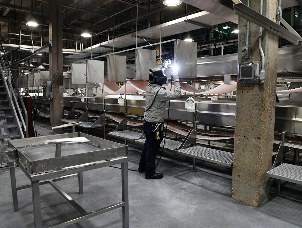 "JBS Greeley Beef Plant welder Guillermo Rivera welds an individual frock hook at each meat processing station that also includes new sheet-metal partitions at each station April 23, 2020. Over 100 employees tested positive for the disease, three plant employees have died, and one (non-plant) JBS corporate employee also passed away. (Photo by Andy Cross/MediaNews Group/The Denver Post via Getty Images)""n""n""n""n"