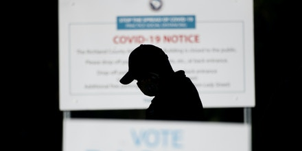 COLUMBIA, SC - OCTOBER 06: A man stands in line outside of the Richland County Voter Registration & Elections Office on the second day of in-person absentee and early voting on October 6, 2020 in Columbia, South Carolina. Polling places have opened in several counties for voters to return their absentee ballots and vote early ahead of Election Day on November 3. (Photo by Sean Rayford/Getty Images)