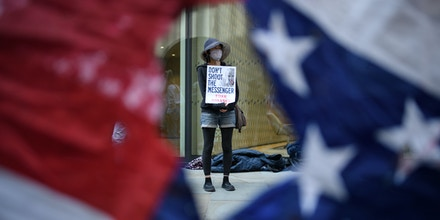 Supporters of the WikiLeaks founder Julian Assange are seen through a torn U.S. flag as they gather outside the Old Bailey in London on Sept. 14, 2020.