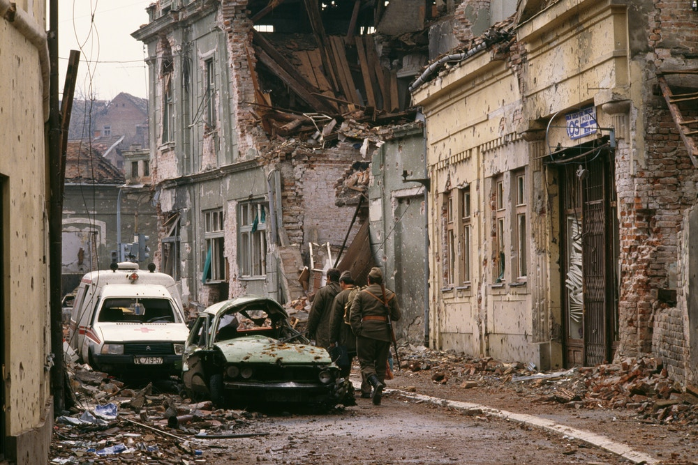 "Yugoslavian soldiers and Serb paramilitaries, including Zeljko ""Arkan"" Raznatovic, walk past bombed buildings riddled with bullet holes and streets filled with rubble after a three-month battle between the Croatian armed forces and the Yugoslavian Federal Army in Vukovar. The Yugoslavian Federal Army completely destroyed the Croatian city, killing thousands of civilians, while the Serbian Volunteer Guard, formed by Raznatovic, was responsible for massive ethnic cleansing campaigns against Bosnian Croats. (Photo by Antoine GYORI/Sygma via Getty Images)"